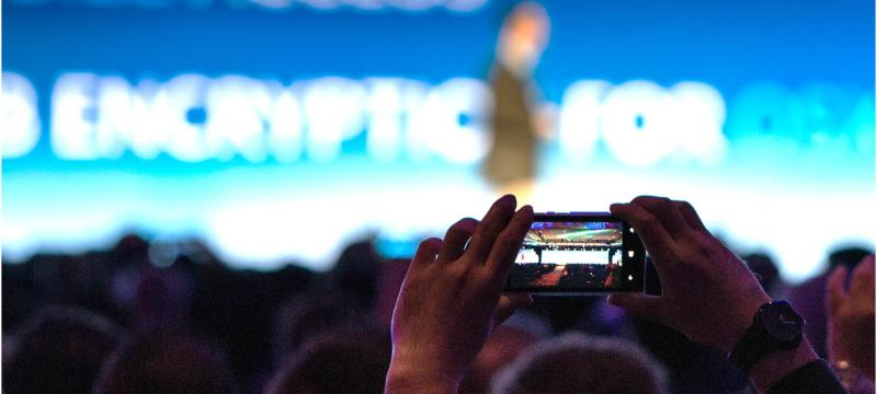 Event attendee taking a photo of the stage with their smartphone