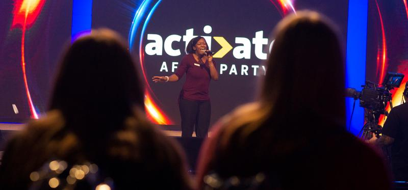 Woman singing karaoke on stage at a corporate event